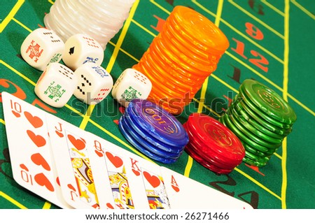 Casino chips,playing bones and royal flash combination on green felt - stock photo