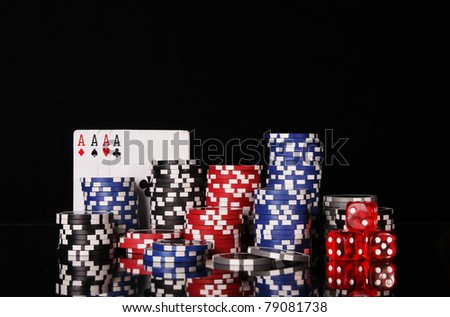 Casino chips with four aces on black background - stock photo