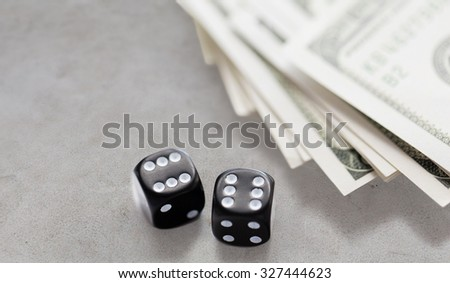 casino, gambling and fortune concept - close up of black dice and dollar cash money on gray concrete table - stock photo