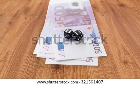 casino, gambling and fortune concept - close up of black dice and euro cash money on wooden table background - stock photo
