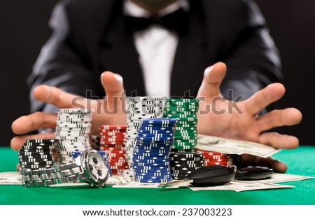 casino, gambling, people and entertainment concept - close up of poker player with chips, money and personal stuff at green casino table - stock photo