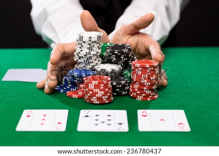 casino, gambling, poker, people and entertainment concept - close up of poker player with playing cards and chips at green casino table - stock photo