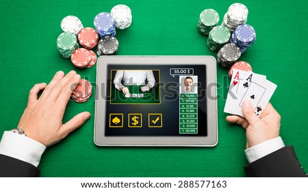 casino, online gambling, technology and people concept - close up of poker player hands with playing cards, tablet pc computer and chips at green casino table - stock photo