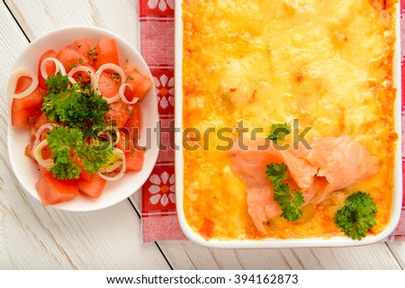 Casserole with smoked salmon, potatoes, leek and cheese. - stock photo