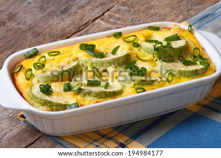 Casserole with zucchini in a white dish close up on a horizontal table  - stock photo