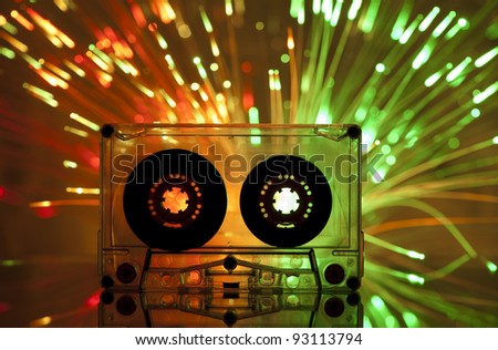 Cassette tape and multicolored yellow green lights on background - stock photo
