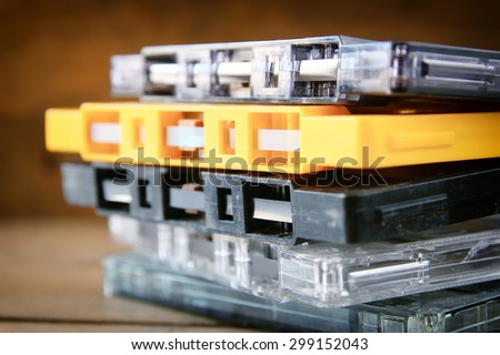Cassette tape over wooden table with tangled ribbon. top view. retro filter  - stock photo