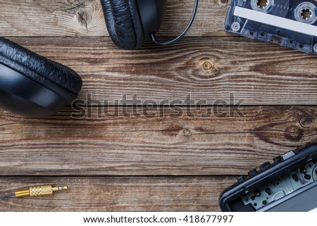 Cassette tapes, player and headphones over wooden table. top view. - stock photo