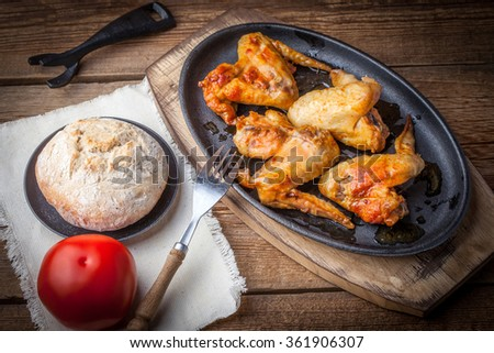 Cast iron frying pan with roasted chicken wings. Selective focus. - stock photo