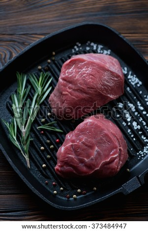 Cast-iron grill with raw fillet mignon steaks and seasonings - stock photo