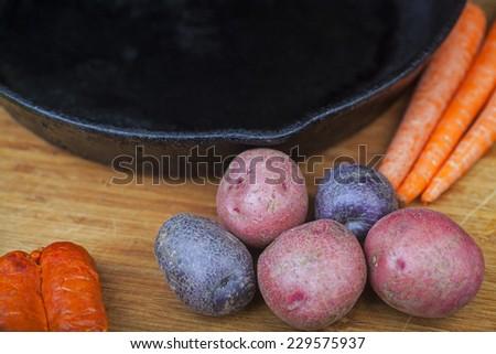 Cast iron skillet on wood cutting board with potatoes, chorizo & carrots - stock photo