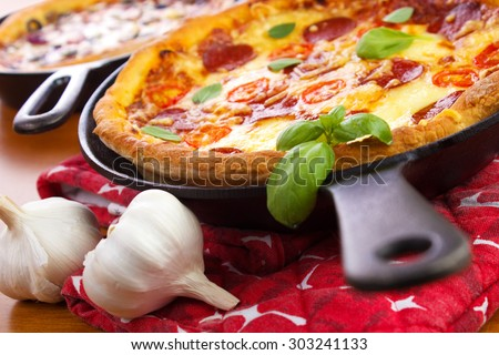 Cast iron skillet pan pizzas with garlic bulbs on wooden table closeup - stock photo