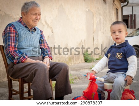 CASTEL SAN GIMIGNANO, ITALY- APRIL 21;Italian grandfather on old wooden chair in lane  caring for grandson looking towards camera on a red toy motor scooter  on April 21, 2011 in san Gimignano, Italy  - stock photo