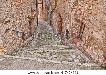 Castiglione d'Orcia, Siena, Tuscany, Italy: picturesque old narrow alley with staircase in the medieval village  - stock photo