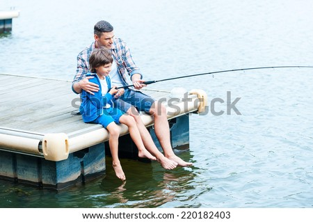 Casting off together. Top view of father and son fishing together on quayside - stock photo