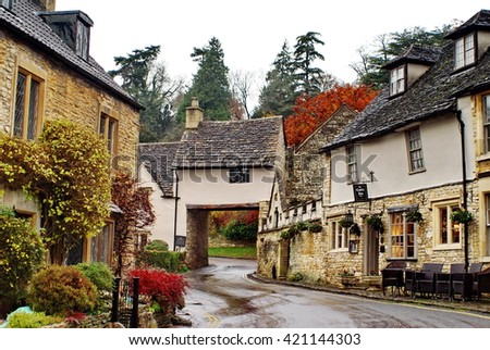 CASTLE COMBE, ENGLAND - CIRCA NOVEMBER 2012: Quaint homes and businesses along the main street, with one structure built on a bridge over the road - stock photo