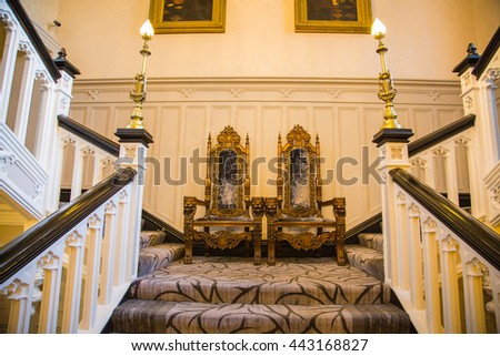 Castle hotel hall interior. Two chairs standing in the middle of the stairs. Mighty classic medieval chairs. - stock photo