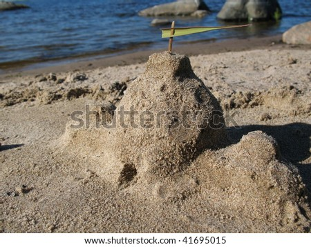 Castle made of sand on lake beach - stock photo
