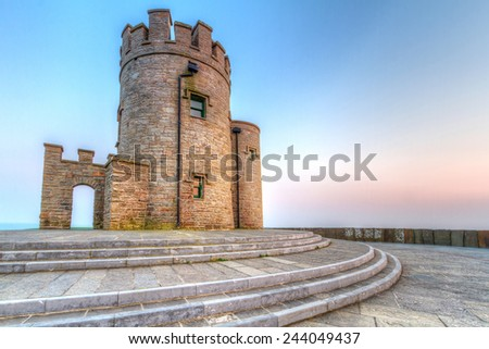 Castle tower on Irish Cliffs of Moher at sunset - stock photo