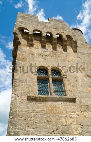 Castle tower with double lancet window in a blue sky - stock photo
