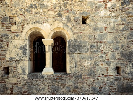 Castle window in a medieval style. Double arched window on a facade of medieval wall. Biforium - ancient window with column, old architecture element of Roman and Gothic styles. - stock photo