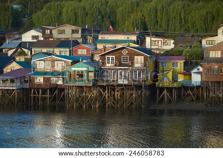 CASTRO, CHILE - JANUARY 14, 2015: Palafitos. Traditional brightly painted wooden houses built on stilts along the waters edge in Castro, capital of the Island of Chilo�©.  - stock photo