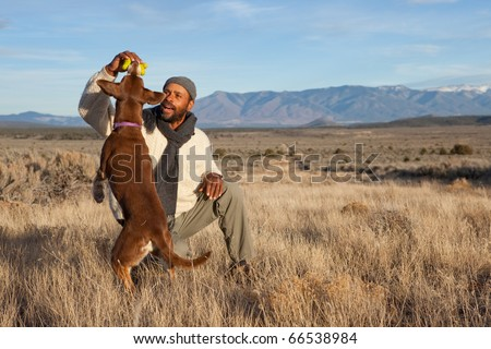 Casual African American man playing with his dog outdoors - stock photo