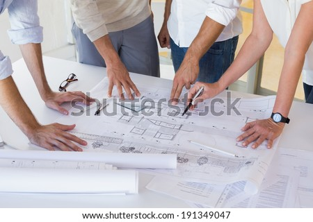 Casual architecture team working together at desk in the office - stock photo