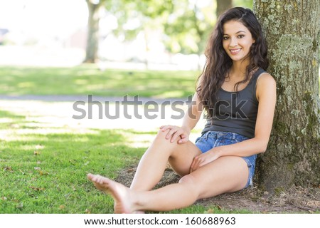 Casual attractive brunette sitting leaning against tree in a park on a sunny day - stock photo