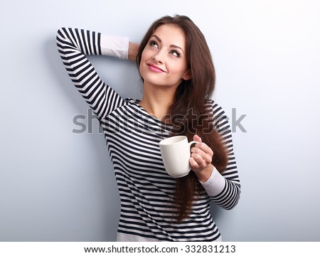 Casual attractive thinking woman holding cup of tea and pensive looking up on blue background - stock photo