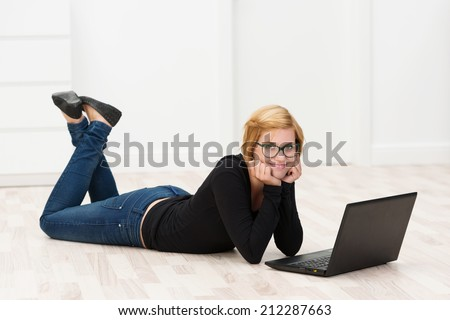 Casual attractive woman working on the floor lying on her stomach with her feet in the air using a laptop computer and smiling at the camera - stock photo