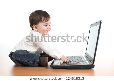 Casual baby smiling while is playing with a laptop computer in a white isolated background - stock photo