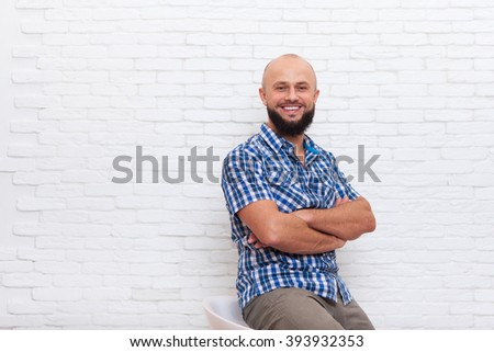 Casual Bearded Business Man Sitting Smiling Folded Hands Office Over White Brick Wall - stock photo