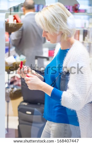 Casual blond young woman buying red lipstick in duty free shop on the airport. - stock photo