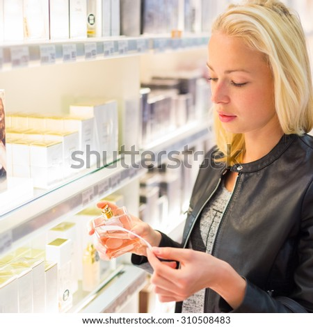 Casual blond young woman smelling perfume in retail store. Beautiful blond lady testing  and buying cosmetics in a beauty store. - stock photo