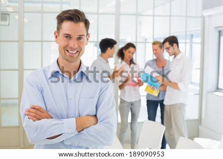 Casual boss smiling at camera in front of his team in the office - stock photo