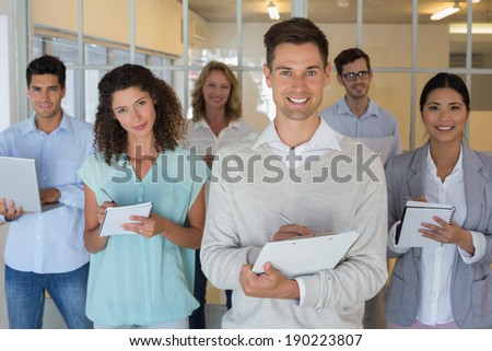 Casual boss standing in front of his team all taking notes in the office - stock photo