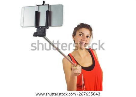 Casual brunette using selfie stick shot in studio - stock photo