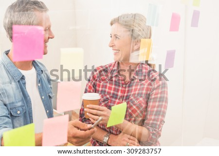 Casual business colleagues laughing at work in the office - stock photo