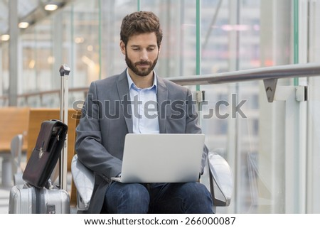 Casual business man working on laptop in airport hall - stock photo