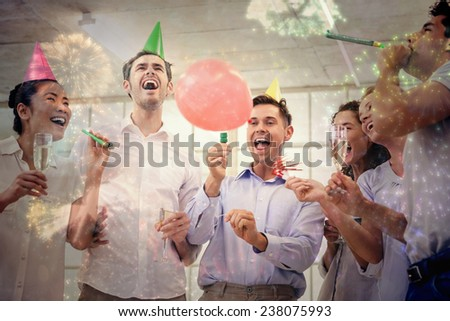 Casual business team celebrating with champagne and party horns against colourful fireworks exploding on black background - stock photo