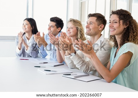 Casual business team clapping at presentation in the office - stock photo