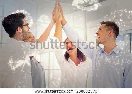 Casual business team high fiving against white fireworks exploding on black background - stock photo