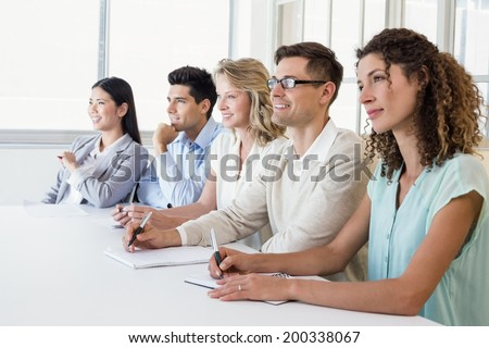 Casual business team listening during meeting in the office - stock photo