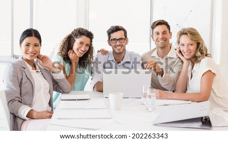Casual business team smiling at camera during meeting in the office - stock photo