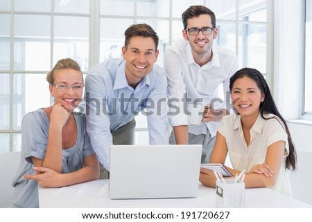 Casual business team smiling at camera together at desk in the office - stock photo