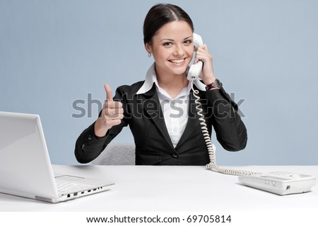 Casual business woman in office working with white table, laptop and talking by phone. Thumbs up! - stock photo