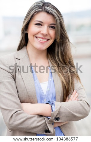 Casual business woman with arms crossed and smiling - stock photo