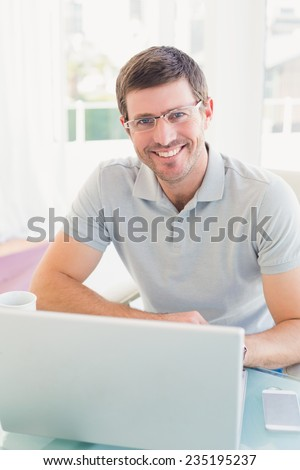 Casual businessman at desk in his office - stock photo