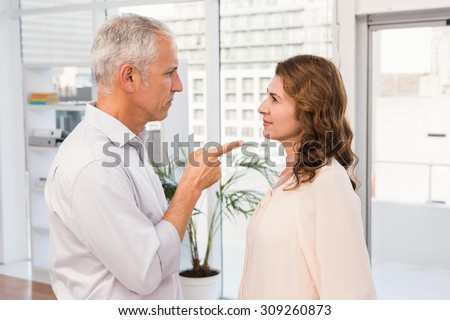 Casual businessman being upset about his colleague in the office - stock photo